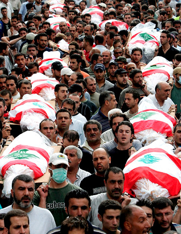 Mourners carry bodies in mass funeral in Beirut 9 August 2006