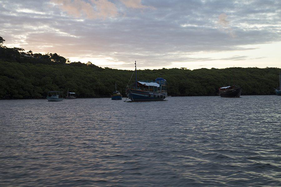 Barquinhos vistos durante o pôr do sol no rio João de Tiba