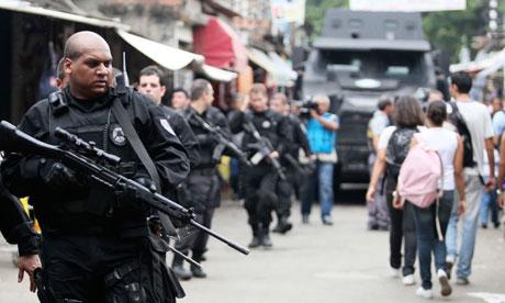 Policemen patrol slum in Rio de Janeiro