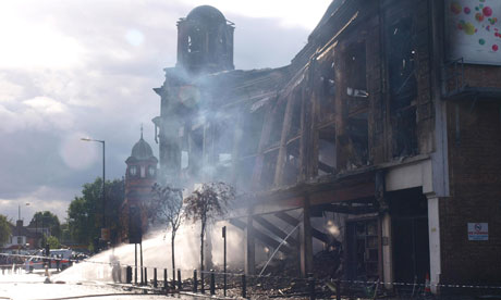 Water is pumped on to a smouldering building in Tottenham, after August rioting