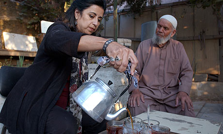 Ahdaf Soueif pours tea while visiting a house in the West Bank