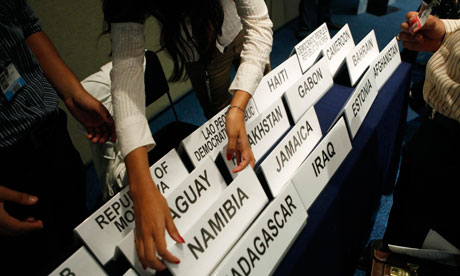 A woman hands out names of countries to participants at the United Nations climate change conference in Cancún, Mexico