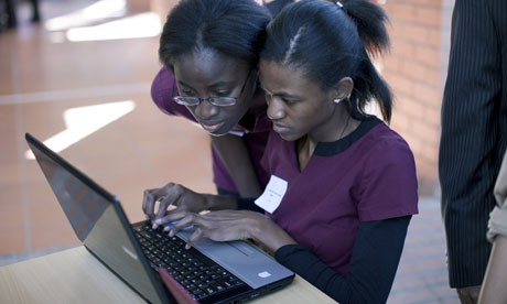 MDG : Social networking in Africa : Two unidentified African students work on a laptop