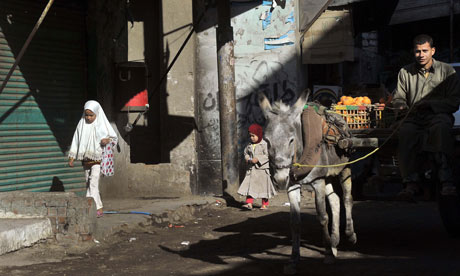 MDG : Egypt : Muslim girls walk past a donkey-pulled cart in the village of Sol, province of Helwan