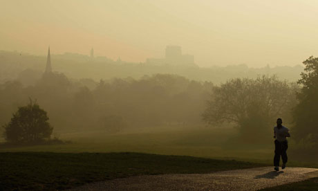 Air pollution in London : A man jogs on Parliament Hill on Hampstead Heath with smog in the distance
