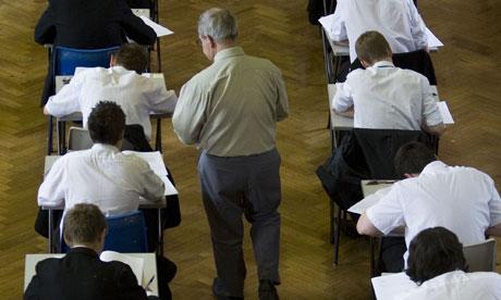 Un vigilante sale del cuadernillo del examen a los escolares pasando un examen