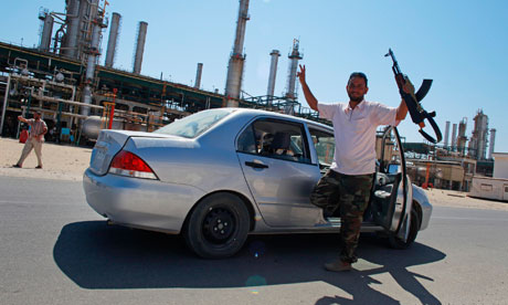A rebel fighter gestures after rebels seized full control of the Zawiyah oil refinery.