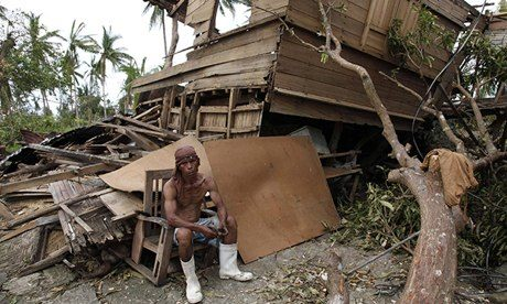 A man takes a break from salvaging reusable woods from his damaged house in Tabogon
