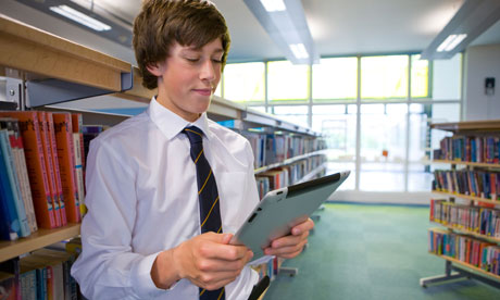 Male student reading electronic book on digital tablet in school library