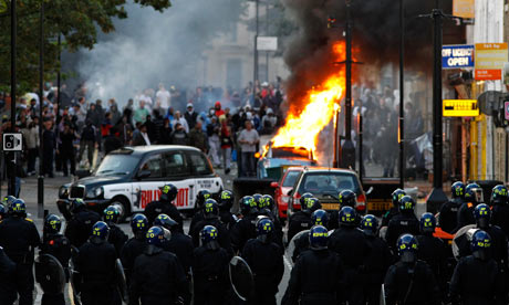 Riots: Police officers in riot gear block a road near a burning car in Hackney, east London