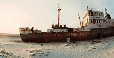 An abandoned ship sitting on the sand in the deserts left by the shrinkage of the Aral Sea.