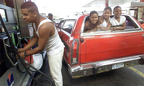 A man fills up his car at a petrol station in Caracas
