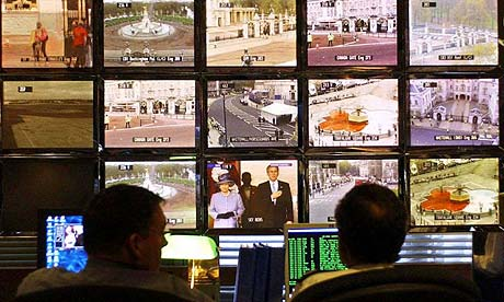 Police officers monitor CCTV screens in the control room at New Scotland Yard in London