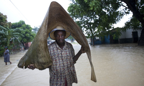 Hurricane Gustav man covers himself with a dry palm leaf in Haiti