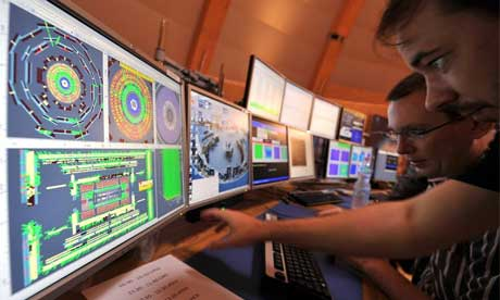 Cern scientists look at computer screens during LHC switch-on
