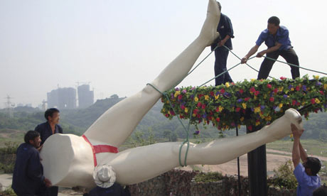 proses pemasangan patung berbentuk selangkangan wanita-pria