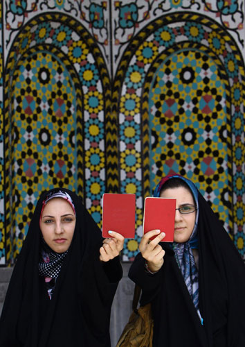 Elections in Iran: Women show their certification cards at a polling station in Qom
