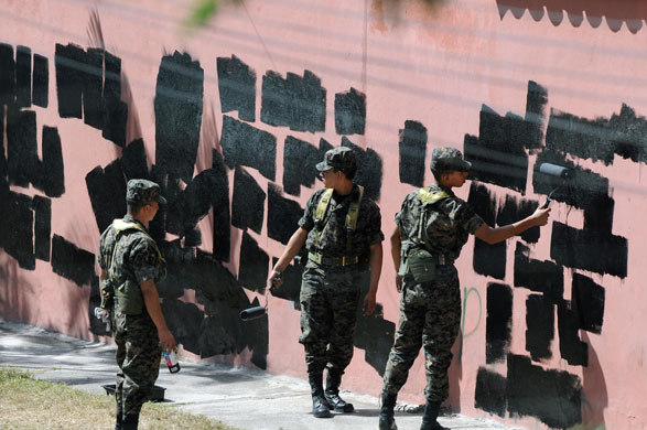 Honduras crisis: Soldiers paint over graffiti on the walls around the Brazilian Embassy