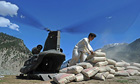 Pakistani man unloads cement from a US military Chinook helicopter