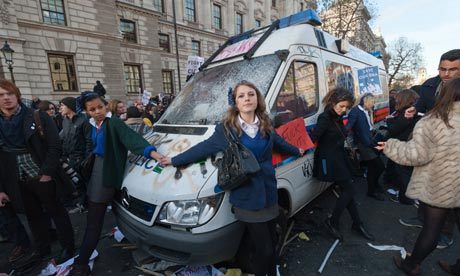 British schoolgirls holding hands around a police van, covered in graffiti.