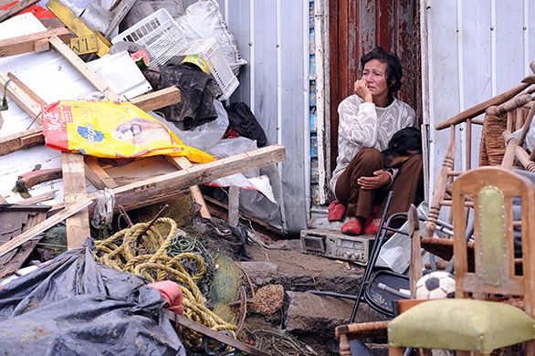 Tsunami damage: A woman sits in her doorway at her house in the village of Penco, Chile