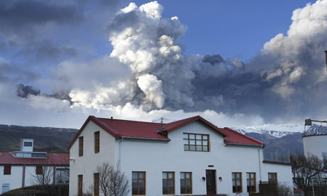 A cloud of ash and steam rises from the Eyjafjallajokull volcano behind a family farm in Iceland