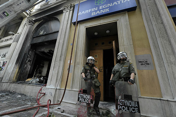 Strike in Greece: Riot police stand in front on burnt out Marfin Egnatia bank