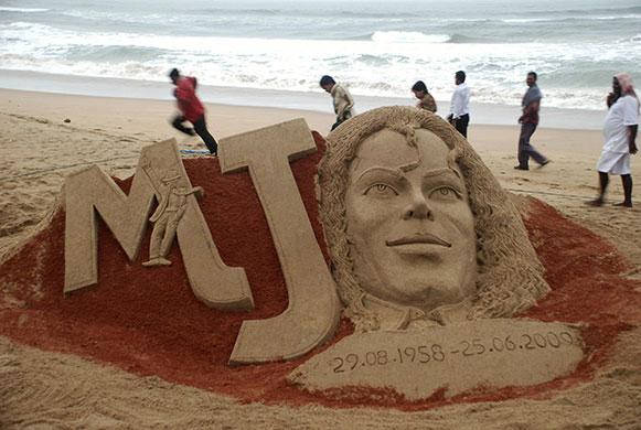 Michael Jackson memorials: People walk past a sand sculpture of Michael Jackson