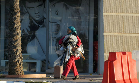 A Tunisian woman carrying clothes walks past a looted supermarket