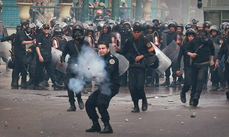 A riot policeman fires tear gas at protestors in Cairo