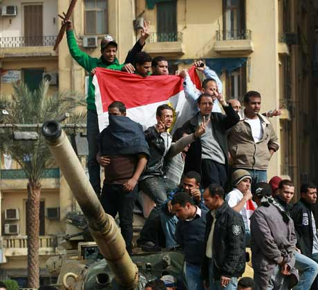 Egyptian protesters stand on an army tank in Tahrir Square, Cairo