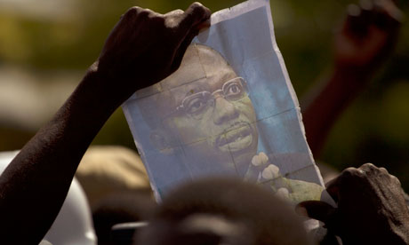 Jean-Bertrand Aristide's picture is held up by a demonstrator protesting against Rene Preval