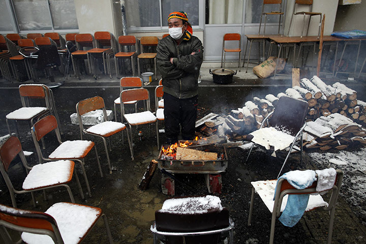 japan disatster: A survivor warms himself by a fire at an emergency shelter in Otsuchi