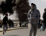 Libyan rebel fighters run for cover after an air force jet drops a bomb on outskirts of Ras Lanuf