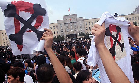 Protesters hold up anti-PX signs in Dalian