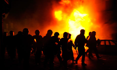 Riot police charge past burning buildings on a residential street in Croydon