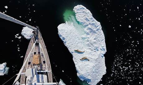 Overhead view of sailboat passing iceberg in Antarctica
