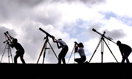 PEOPLE LOOKING THROUGH TELESCOPES