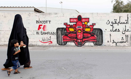 A woman and her child pass in front of anti-Formula One graffiti in the village of Barbar, west of Bahrain's capital Manama. Photograph: Hamad I Mohammed/Reuters