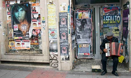 A man plays an accordion in the doorway of a closed down bank branch in Madrid, Spain
