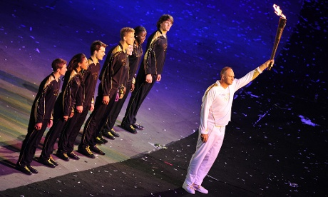 Sir Steve Redgrave holds the Olympic torch aloft at the London 2012 opening ceremony
