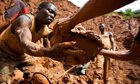 Gold miners form a human chain while digging an open pit in northeastern Congo