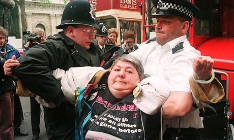 A paraplegic woman is removed from in front of a b
