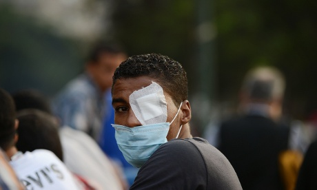 An injured Egyptian protester looks on during clashes with riot police near the US embassy in Cairo.