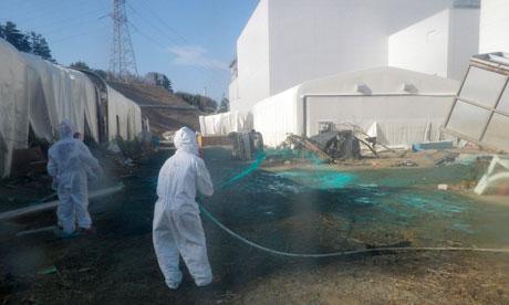Tepco workers spray dust protectant near the Fukushima Daiichi plant