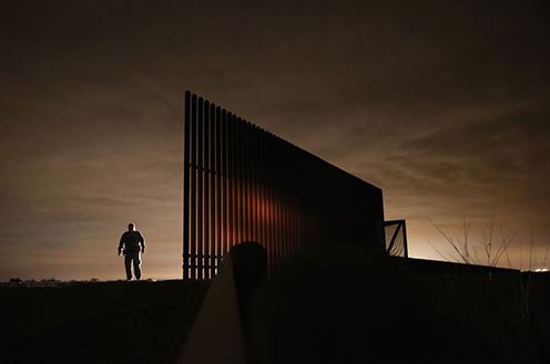 A US border patrol agent stands near a section of the US-Mexico border fence