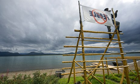 A man erects a flag against the proposed Pebble Mine in Alaska in 2008