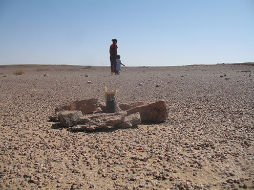 A Saharawi woman and child walk near a mine in the desert