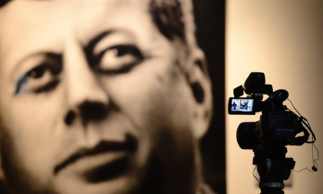 A TV camera sits on a tripod filming a picture of John F. Kennedy inside the Sixth Floor Museum in Dallas, Texas