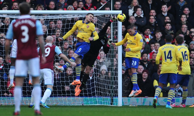Arsenal goalkeeper Wojciech Szczesny punches the ball clear.